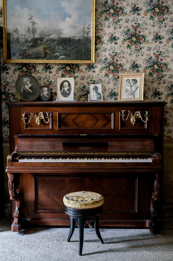 Dark wood piano and floral upholstered piano stool with black and white photo frames
