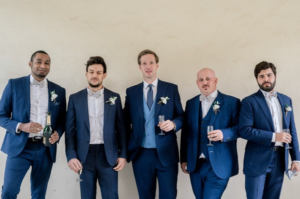 Groom and four groomsmen in blue suits holding champagne glasses