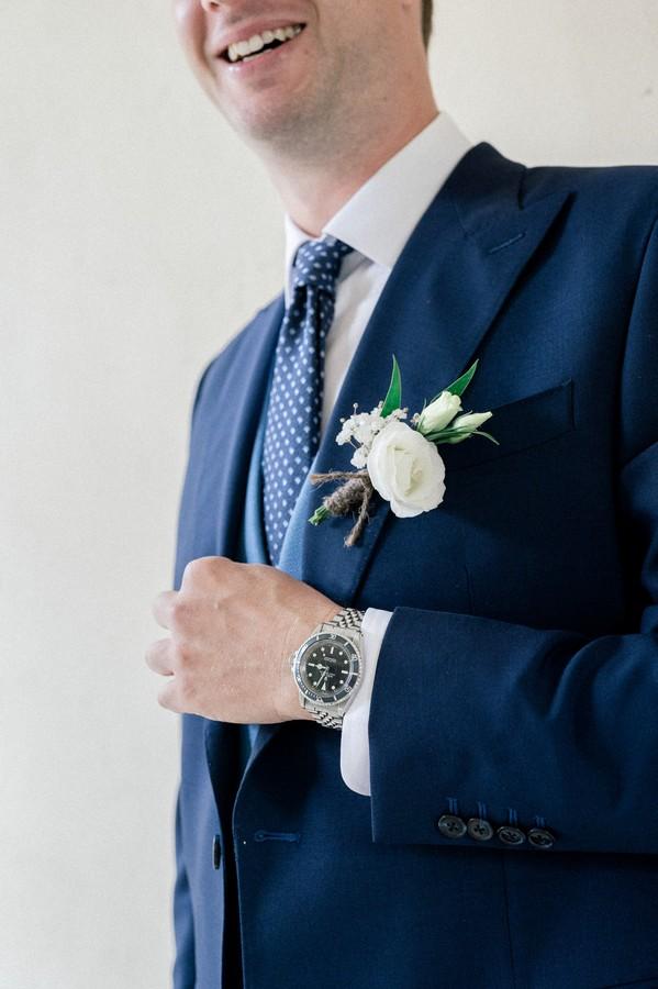 Closeup of groom's cream flower boutonnière on blue suit