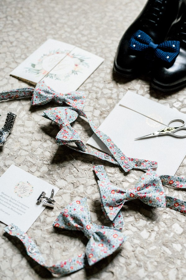 Flat lay of groom shoes, blue bow tie and floral bow ties for grooms men