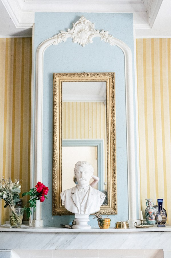 Fireplace, mirror and statue bust inside home in L'Isle-sur-la-Sorgue, France