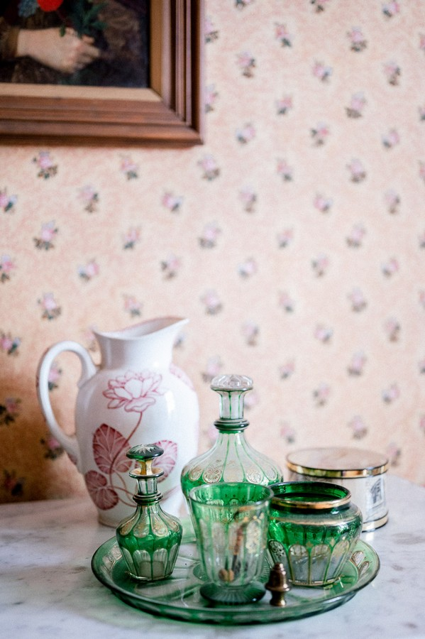 Crystal glassware on plate with ceramic jug in front of floral wallpapered wall