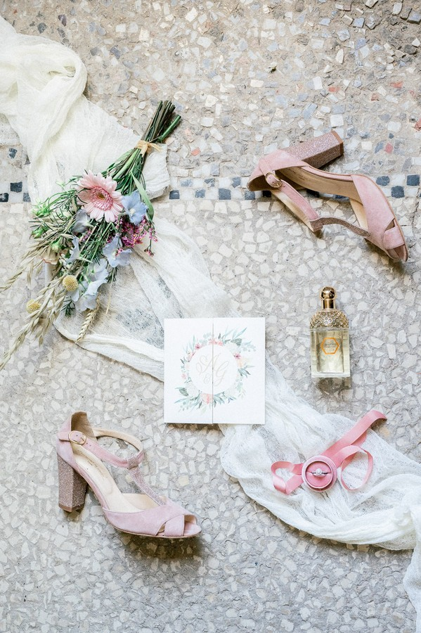 Flat lay of pink bridal shoes, pastel bouquet, floral wedding stationery and perfume