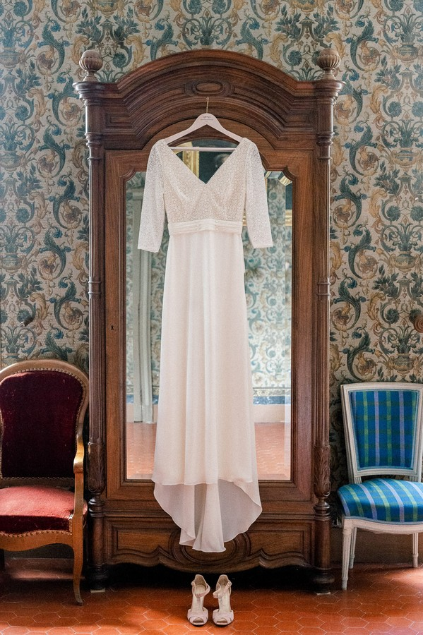 Wedding Dress hanging on the front of mirrored armoire in french wallpapered room