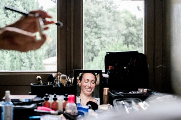 Reflection of bride in mirror getting makeup done