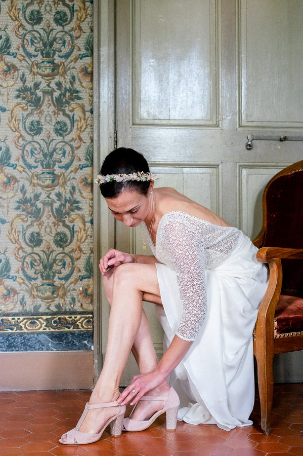 Seated bride fastens her shoe