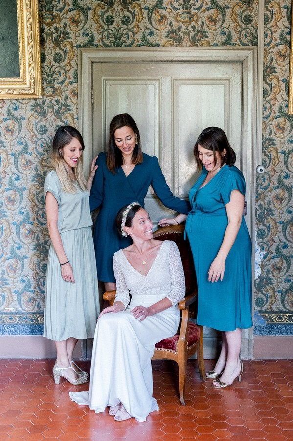 Seated bride surrounded by bridesmaids in various shades of blue bridesmaid dresses