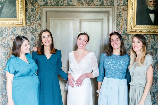 Bride in between her four bridesmaids all wearing various shades of blue dresses