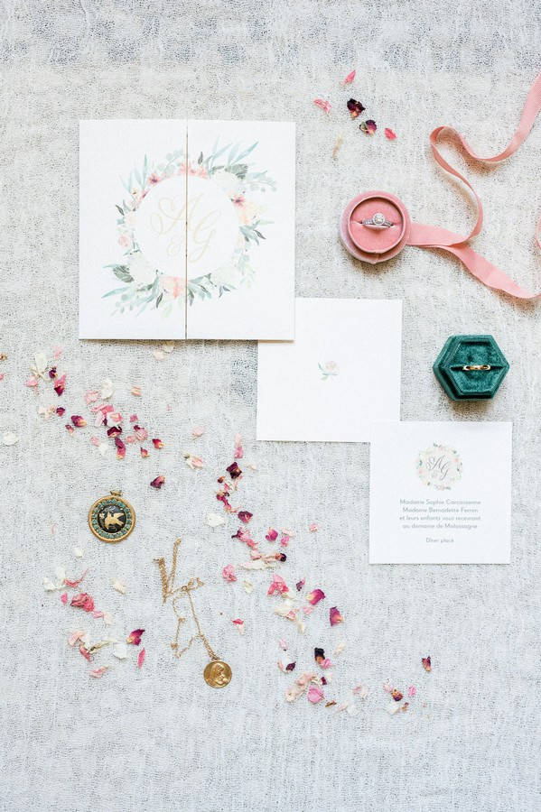 Bridal flat lay of petals, jewellery, ring boxes and floral stationery