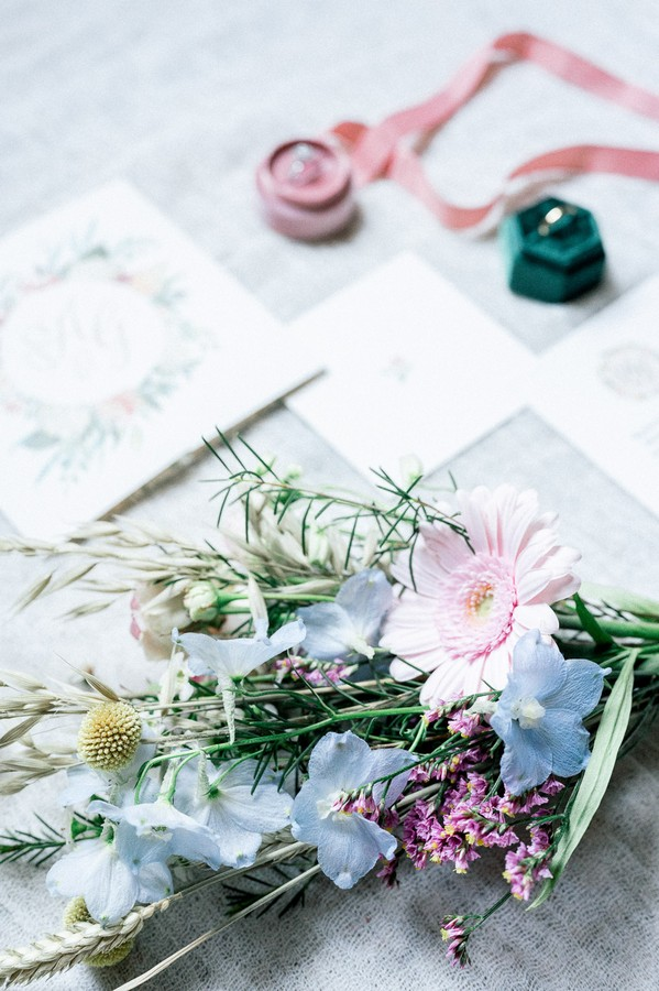 Flat lay of bouquet, pink and green ring boxes and floral stationery