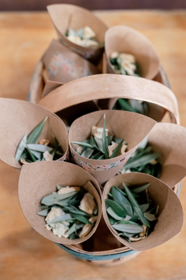 Brown paper cones filled with dried leaves and flowers for confetti