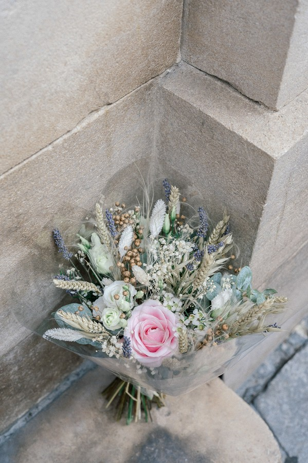 Pastel bunch of flowers leans against sandstone wall