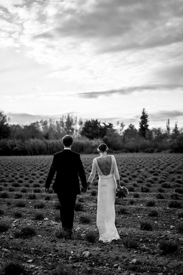 Black and white image of bride and groom walking away from camera through field