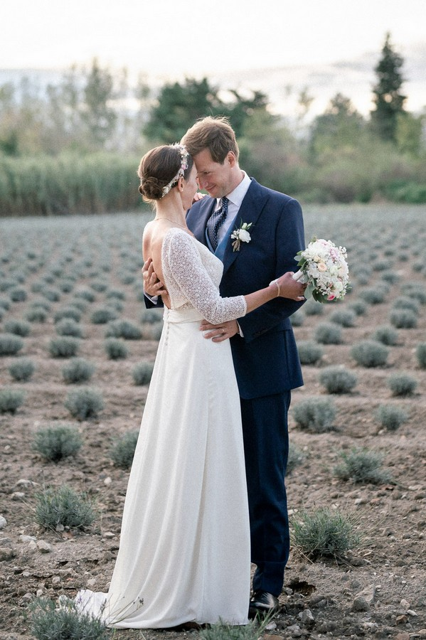 Bride and groom look into each other's eyes in field