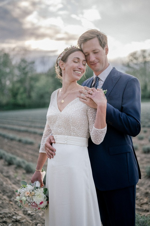 Groom holds his bride's waist in field in France