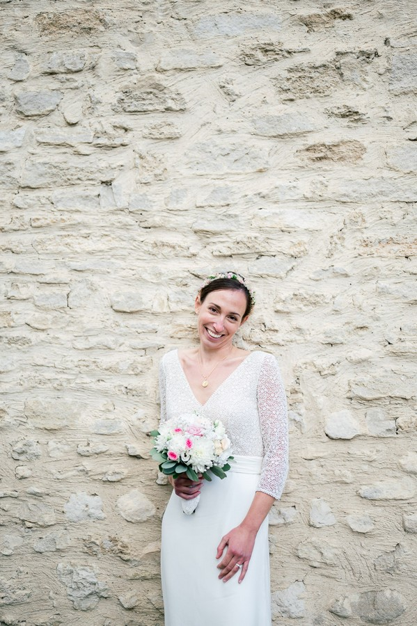 Bride stands with bouquet against rough stone wall