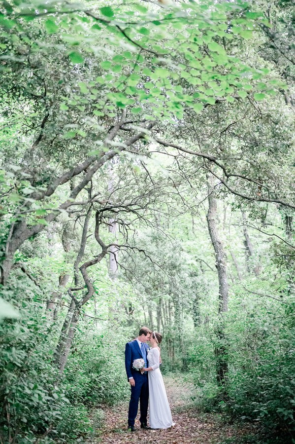 Bride and groom on garden path framed by green trees