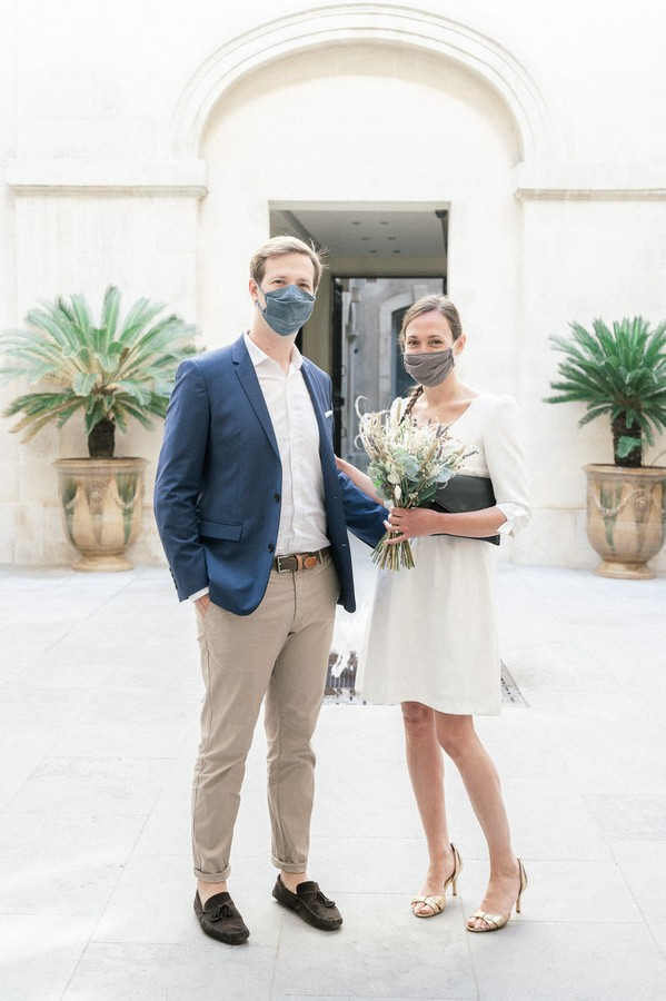 Bride and groom wearing grey facemasks for wedding ceremony