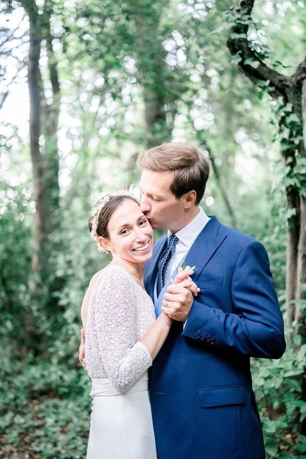 Groom kisses bride's forehead as she smiles to camera surrounded by green trees