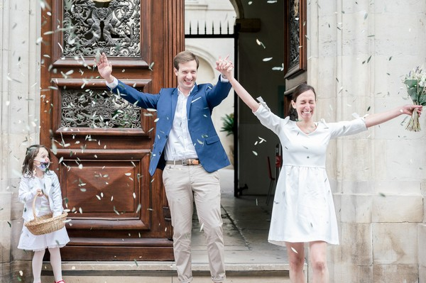 Bride and groom leave town hall with arms in air showered by confetti