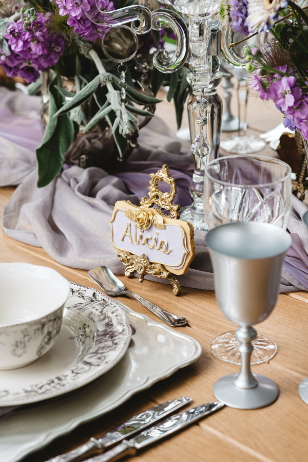purple themed wedding table setting with small gold and purple biscuit name placeholder