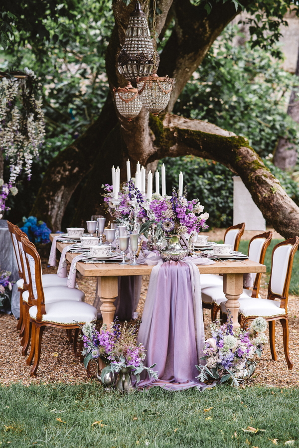 outdoor wedding table setting in purple under tree with crystal chandeliers hanging from its branches
