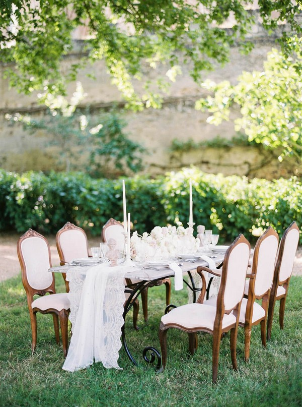 cream outdoor wedding table setting on green lawn under green trees