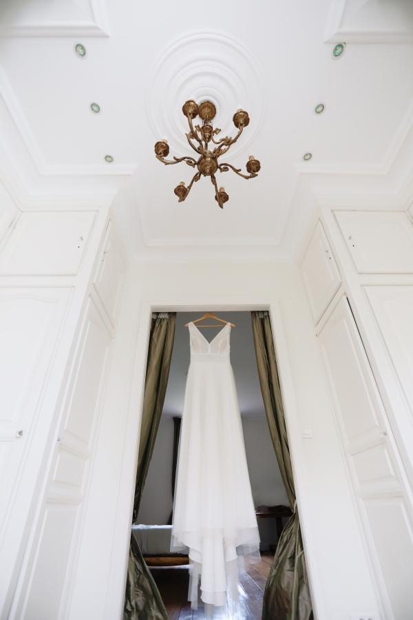 Brides dress hangs in doorway of white room