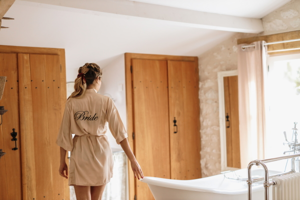 "Bride walks around bathtub in pink silk robe with the word ""bride"" embroidered across the back"