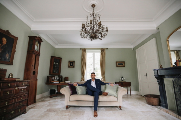Groom in navy blue suit sits with one leg cross and arms outstretched on cream lounge in green room of Chateau Lacanaud in France