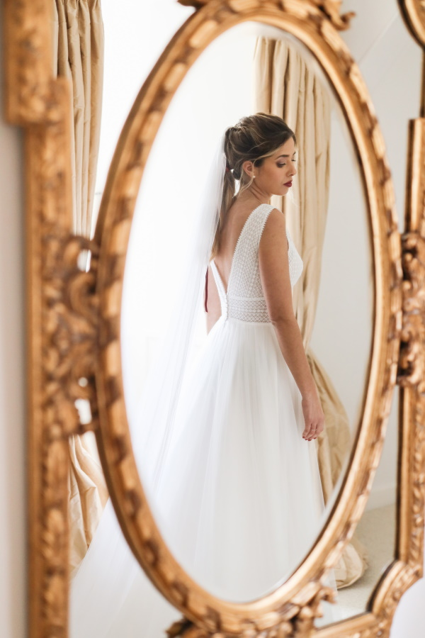 Bride has back turned in reflection through gold gilded mirror