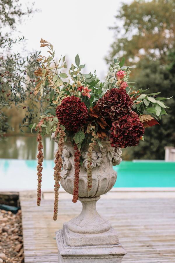 Burgundy, pink and eucalyptus floral arrangement in stone Medici vase