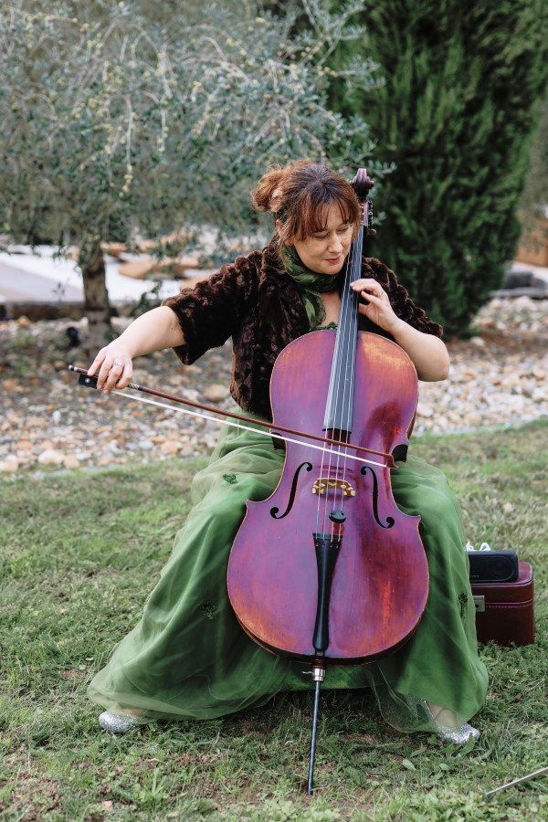 Cellist plays entrance music for bride wearing green skirt in garden of Chateau Lacanaud, Dordogne France