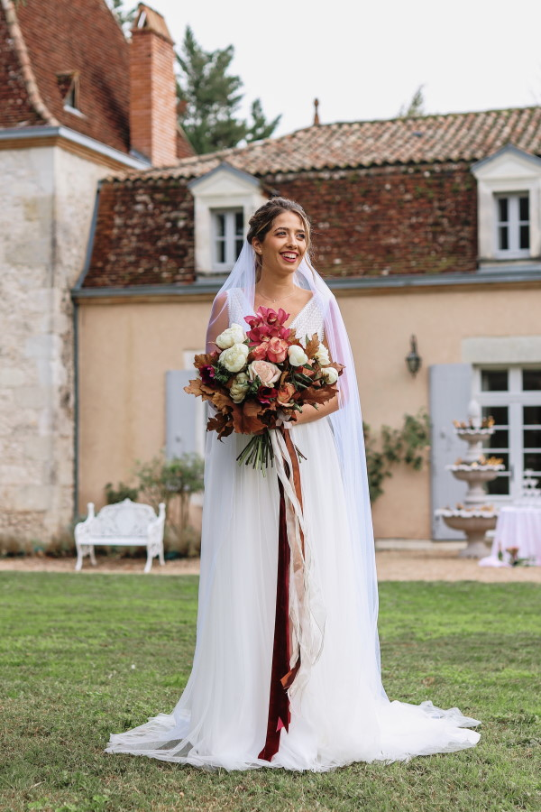 Bride stands outside Chateau Lacanaud holding burgundy and white bouquet and smiles towards her groom