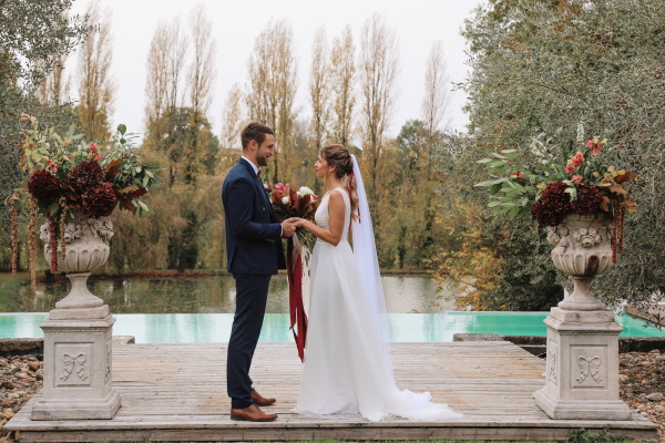 Bride and groom hold hands for their vows in front of outdoor pool