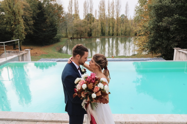 bride and groom lean in for a kiss in front of aqua outdoor pool