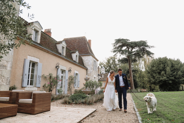 bride and groom walk with dog on lead through the garden outside Chateau Lacanaud in Dordogne France