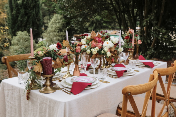 abundant outdoor wedding table decorated with burgundy and pink floral arrangements and tableware