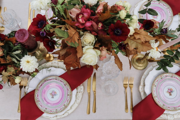 brides bouquet is laying on wedding table with burgundy flowers and table decorations and golden cutlery