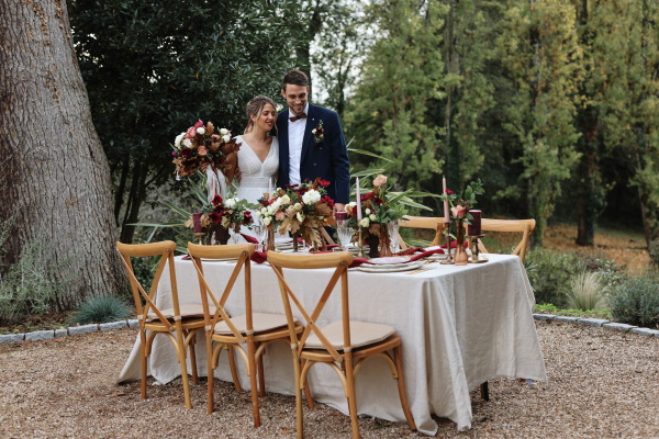 bride and groom stand behind their outdoor wedding table adorned in white table cloth and burgundy and pink table decorations