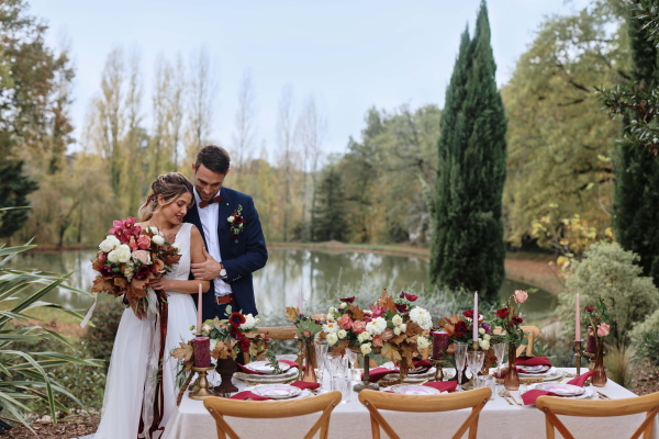 bride and groom stand at wedding table in front of outdoor lake and tall green trees