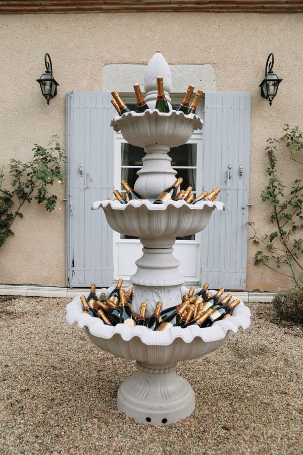 champagne bottles fill a 3 tier outdoor stone water fountain for wedding guests