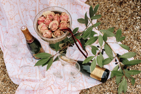 flatlay image of a bowl of pink roses, 2 bottles of champagne, a pink picnic rug and eucalyptus leaves