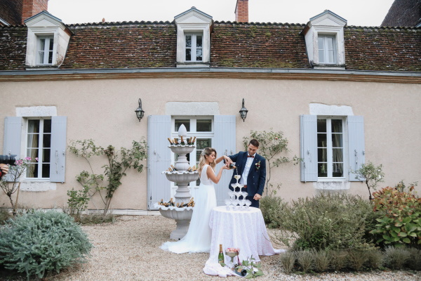 bride and groom begin pouring champage into champagne tower at chateau lacanaud