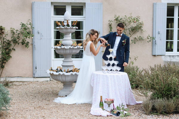 bride and groom laugh as they pour champagne into a champagne glass tower outside chateau lacanaud