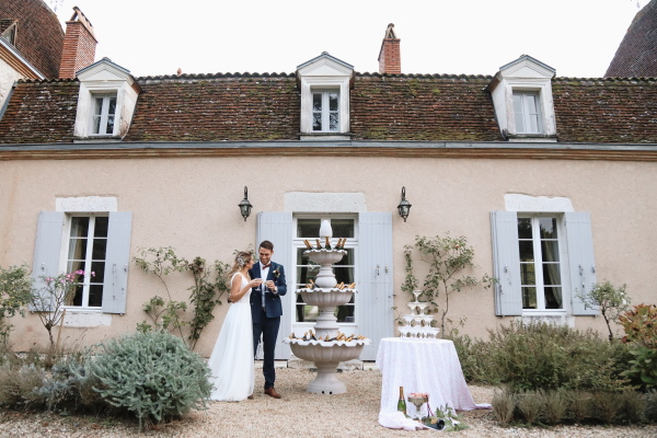 standing outside chateau lacanaud in dordogne france, bride and groom toast their wedding day next to fountain of champagne bottles