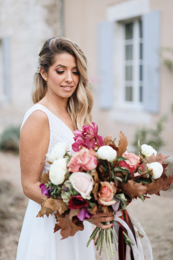 bride smiles and looks down at bouquet of burgundy and pink flowers