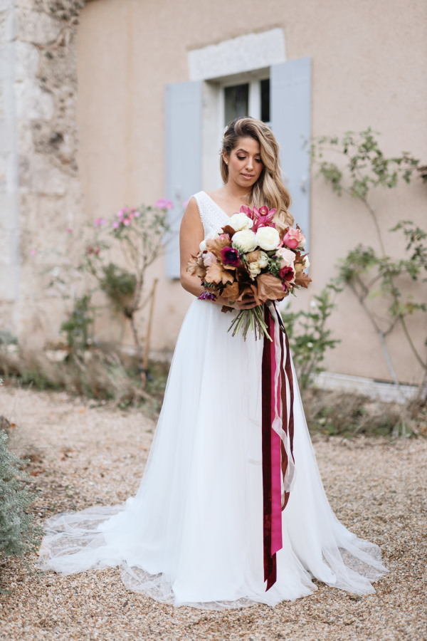 bride stands outside chateau lacanaud in france wearing white flowing bridal gown and holds burgundy large bouquet with long burgundy ribbons
