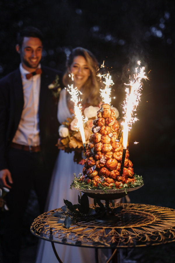 bride and groom smile as sparklers ignite on their croquembouche in the dark