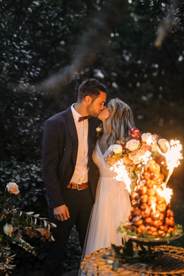 bride and groom kiss in the sparkler light as they cut their croquembouche